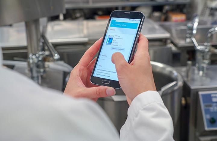 Person i arbeidssituasjon benytter HygiNet på smarttelefon; hygienearbeid blir enkelt med denne tjenesten.